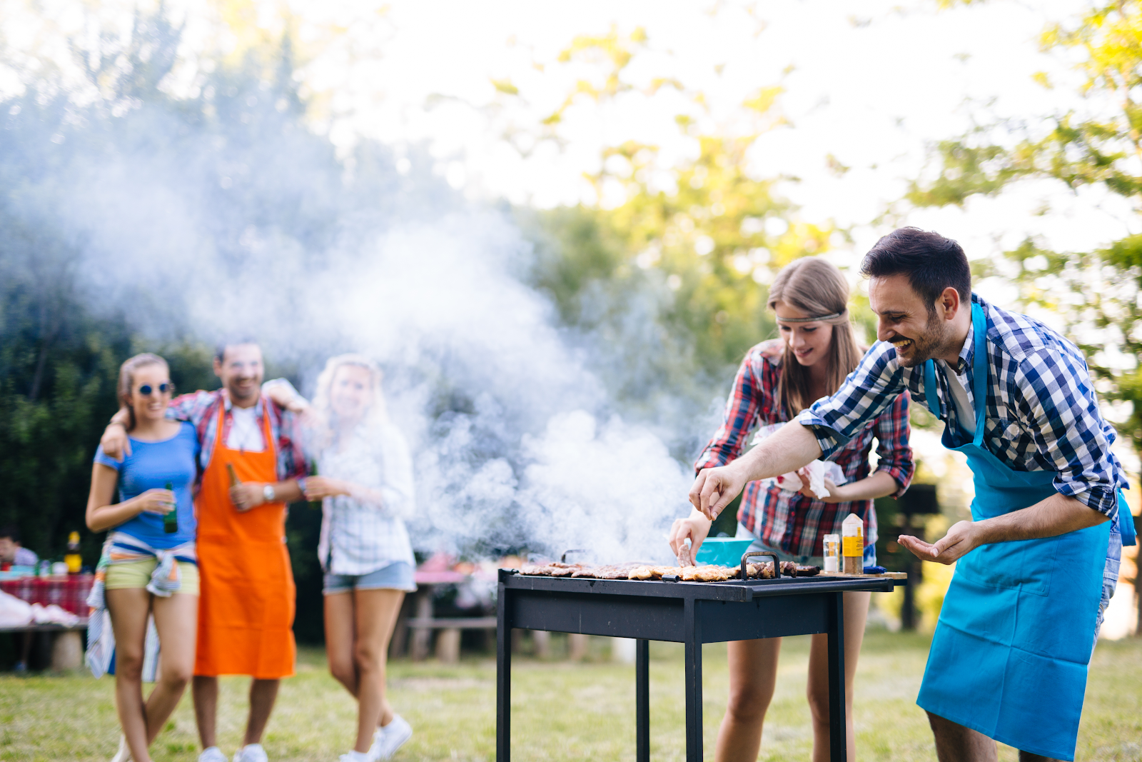 A family enjoys the outdoors while the father cooks on a grooved outdoor griddle