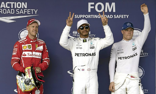 Mercedes driver Lewis Hamilton, centre, after qualifying for the US Grand Prix with Ferrari's Sebastian Vettel, left, and Mercedes team-mate Mercedes driver Valtteri Bottas, at Circuit of the Americas in Austin, Texas. Picture: JEROME MIRON-USA TODAY SPORTS