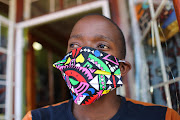 Nhlanhla Nkosi poses for a picture with his fashionable mask, on March 25 2020, at Nkosibo Laundromat and Dry Cleaners in Melville, Johannesburg. The idea to make fashionable masks came when owner Suzan Mazibuko couldn't find the surgical masks in shops, most being sold out. She got to work and started production using brightly coloured fabrics, cartoon characters and Ndebele patterns which she sells for R30. They are not surgical quality but can be used to accessorise the hospital grade mask. Her small business will be closed over the 21-day lockdown.