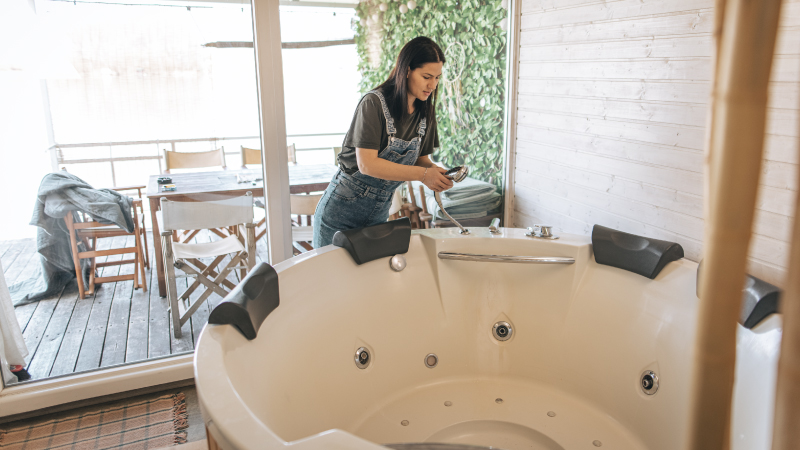 A woman cleaning her hot tub before moving it