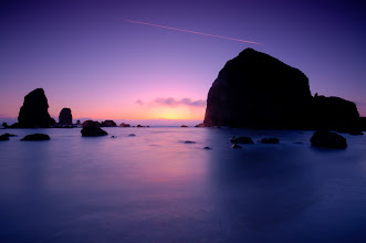 Photo: Haystack Flyby  There's a pilot out there who may never know he graffiti'd the sky during my shot. I almost cloned it out but decided to leave it because, well, it was there. On Friday my son and I left my wife and daughter behind to knit and read while we watched the sunset at Haystack Rock. Okay, he didn't watch it, he ran around the beach looking for a place to pee play while I shot pictures. I'm thankful that my family is patient with me and this photography thing, they are the best!  When Alex and I got to this spot it was swarming with people and lots of other photographers. The tide was low so you could walk out to the rock and explore the tide pools which were teaming with starfish. All the while thousands of seabirds were feasting on the rocks. So I pulled out my ND filters and set the tripod (yes, I remembered my tripod shoe) for some long exposures. This helped smooth out the water and hide the people lurking in the right hand part of the frame. Plus a good ND filter really helps bring out the colors in the sky.  #blog