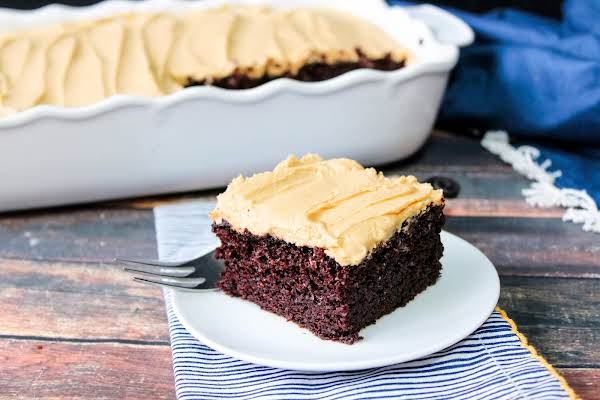A Slice Of Homemade Chocolate Cake With Peanut Butter Frosting On A Plate.