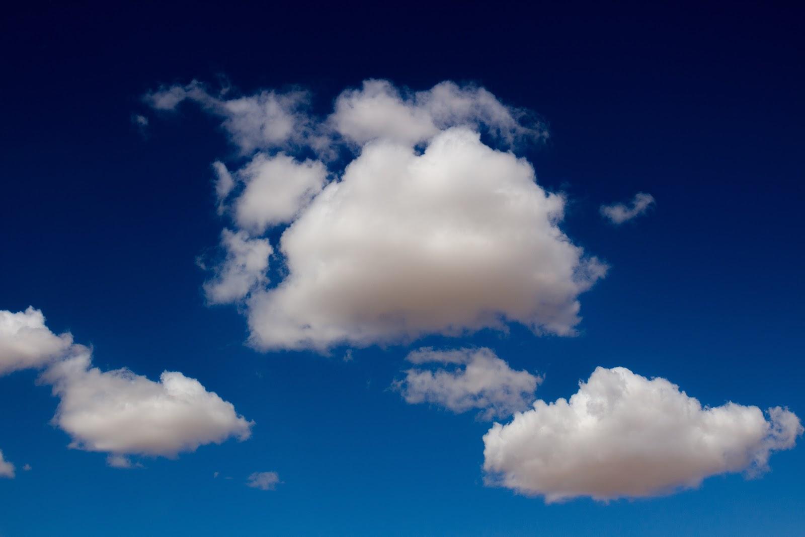 a few white clouds in front of a dark blue sky