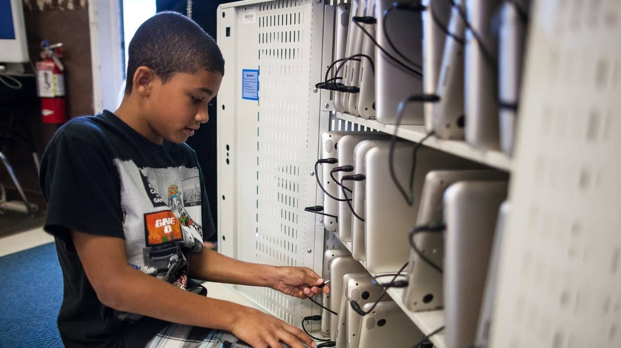 A student in a room filled with Chromebooks on shelves.