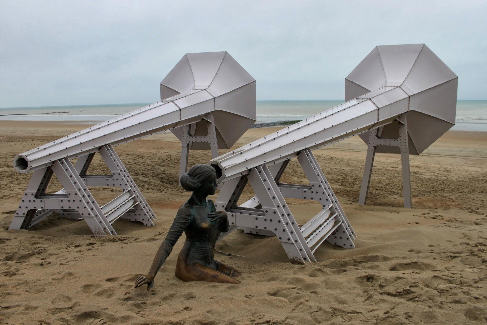 """Photo: """" I Can Hear It """" bestaat uit twee hoorns (gelijkend op oude grammofoons), gericht naar de zee. Op een bank voor de hoorns zit een vrouw die haar oor te luisteren legt.Kunstwerk van Ivars Drulle."""