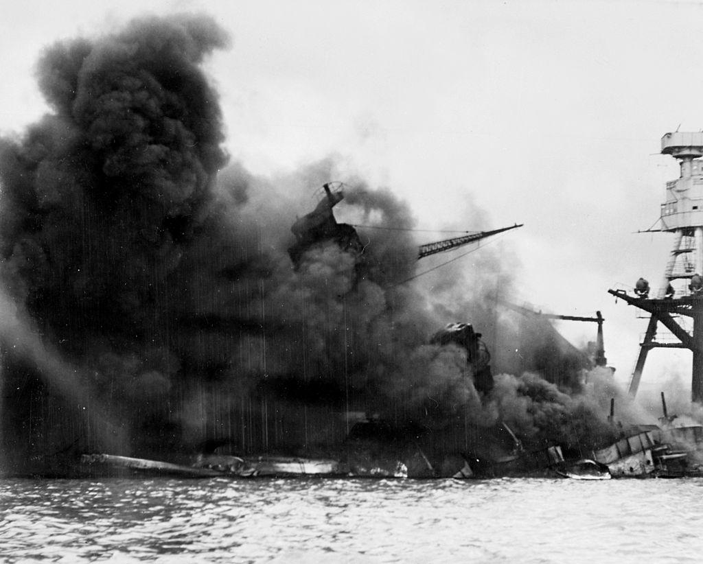 The US battleship Arizona in flames, sinking into Pearl Harbor.
