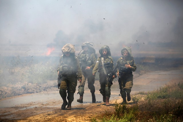 Israeli soldiers patrol near a burning field on the Israeli side of the border between Israel and Gaza, May 14, 2018.