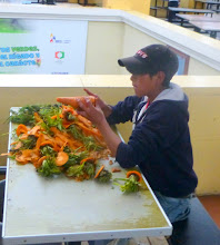 Photo: Young man with the chore of peeling carrots, Central Market