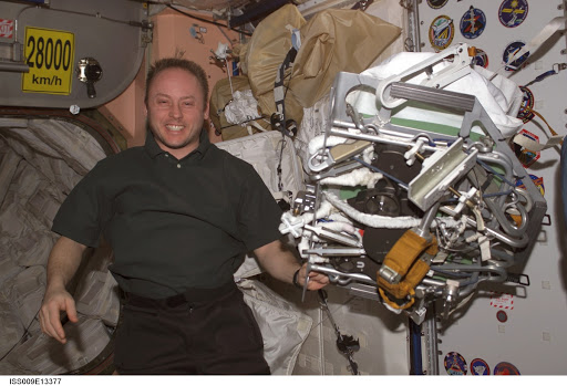 Fincke poses with a packed EVA tool and gear bundle in Node 1 during Expedition 9