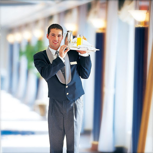 A smart-looking butler delivers breakfast on a Crystal cruise.