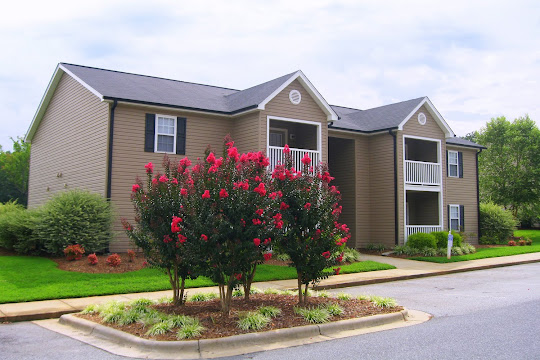 Matthew Grande apartment building with brown siding and flowering trees