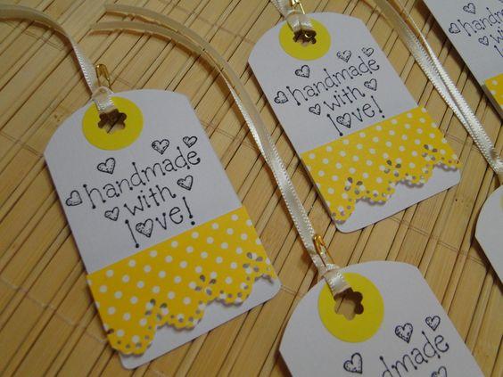 """Tags de papel para decorar seus produtos artesanais. <br> <br>O Kit é composto por: <br>- 5 tags feitas com papel branco padrão linho, decoradas com papel e adesivo colorido (amarelo e branco), furadores, carimbo (com a frase """"Handmade with love"""", ou seja, """"Feito a mão com amor), fita de cetim e mini alfinete. <br> <br>** Você que adora fazer trabalhos crafts, pode incrementar seus produtos com essas delicadas tags (etiquetas).**"""