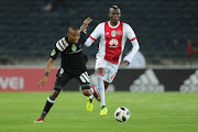 Orlando Pirates' defender Gladwin Shitolo (L) shields the ball away from Ajax Cape Town striker Tendai Ndoro (R) during the Nedbank Cup Last 32 match at Orlando Stadium on February 10, 2018 in Johannesburg, South Africa.