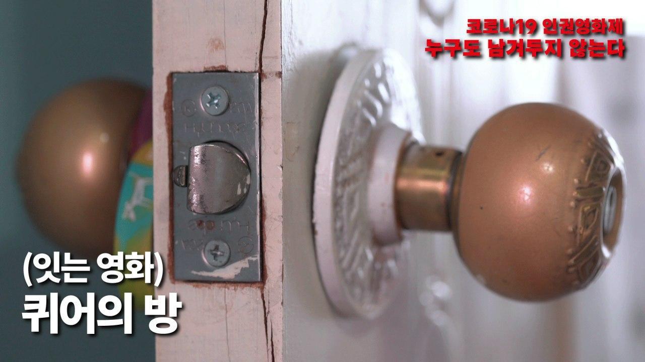 사진8. 영화 퀴어의 방의 스틸컷. 낡은 방 문 손잡이. 양 쪽 손잡이가 보이고 문 걸쇠가 사진 가운데 있다. 그리고 걸쇠 옆을 위에서 아래로 가로지르는 긴 금이 있다. 걸쇠를 기준으로 왼쪽 손잡이에는 동물 그림이 있는 손목 밴드가 걸려있다. 오른쪽 손잡이는 칠이 벗겨져 있다.