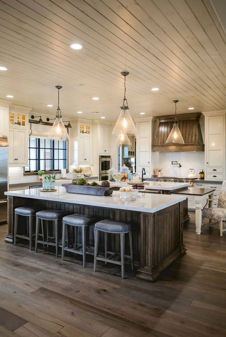 Modern farmhouse kitchen with pendant lighting, large wood island, marble countertops, wood floors and shiplap ceiling