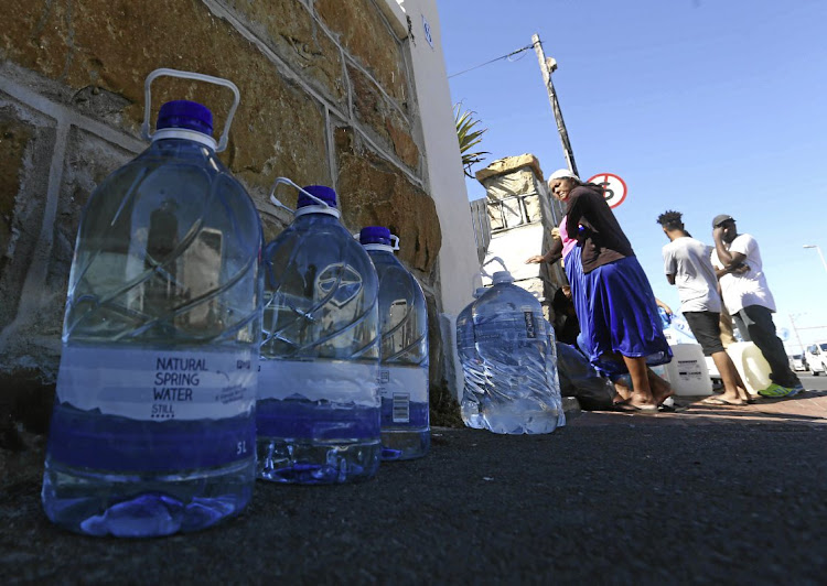 People queue to fill up water bottles at Muizenberg spring in Cape Town.