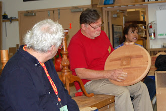 Photo: Ernie was here to teach a class in making a tilt-top table.  Richard Webster examines a table top from the class.
