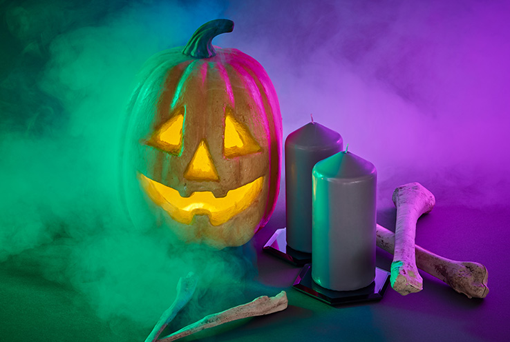 Carved pumpkin next to candles and bones shrouded in smoke