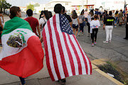 People with the Mexican flag and the US flag take part in a rally against hate a day after a mass shooting at a Walmart store, in El Paso, Texas, US, on August 4 2019.