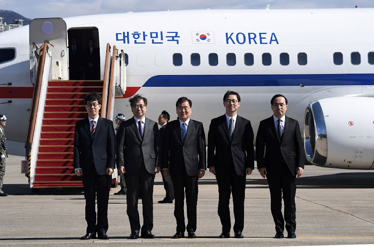 Chung Eui-yong, head of the presidential National Security Office, Suh Hoon, chief of the South's National Intelligence Service, and other members of South Korean delegation pose before boarding an aircraft as they leave for Pyongyang at a military airport in Seongnam, south of Seoul, South Korea, on March 5 2018. Picture: REUTERS/JUNG YEON-JE/POOL