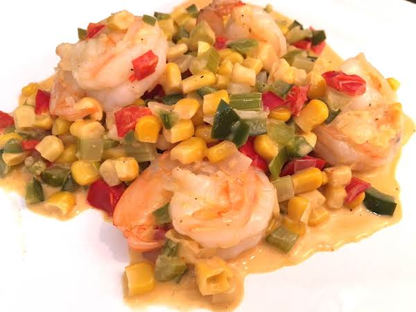 A Few Cooked Shrimp With A Mixture Of Corns, Bell Peppers In A White Sauce Served On A White Plate.