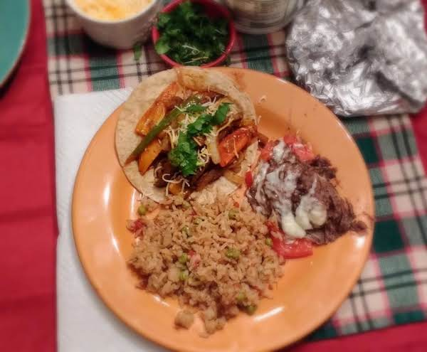 Beef Fajitas Served With Mexican Rice And Refried Black Beans.