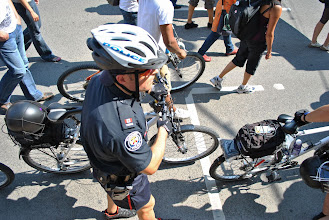 Photo: A police officer walks his bicycle along a protest route.