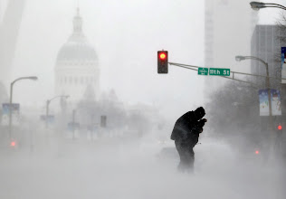 Photo: A person struggles to cross a street in blowing and falling snow Sunday, Jan. 5, 2014, in St. Louis. Snow that began in parts of Missouri Saturday night picked up intensity after dawn Sunday with several inches of snow on the ground by midmorning and more on the way. (AP Photo/Jeff Roberson)