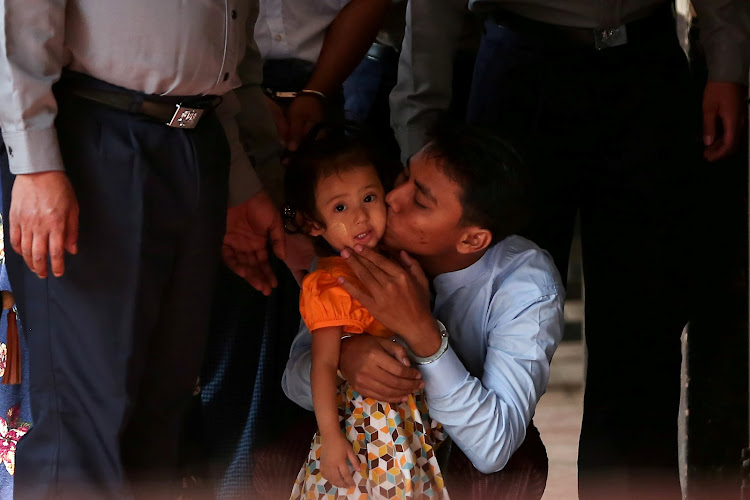 Detained Reuters journalist Kyaw Soe Oo kisses his daughter as he is escorted by police for a court hearing in Yangon, Myanmar.
