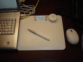 Wacom Bamboo Fun 白色放在一台电脑旁边。