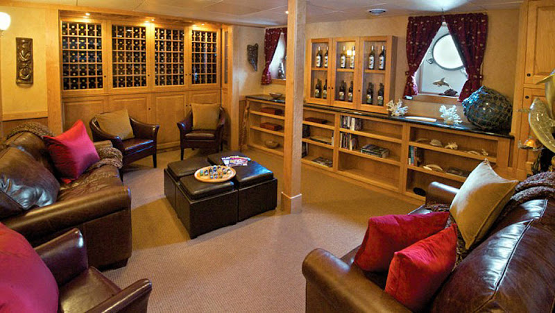 A spacious salon/wine library features cozy chairs and a large flat-screen TV.