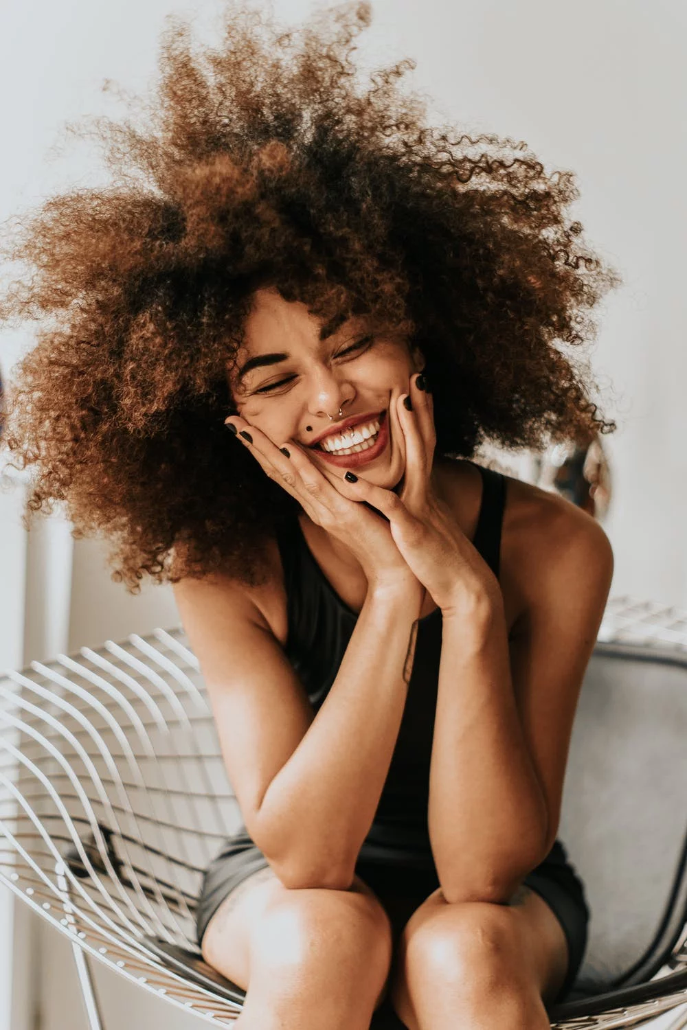 woman with curly hair laughing