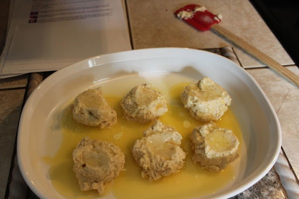 Drop biscuit dough by spoonfuls into the baking dish, with the melted butter already...