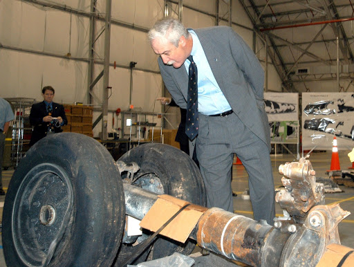 In the RLV Hangar NASA Administrator Sean O'Keefe examines a piece of debris from Space Shuttle Columbia.