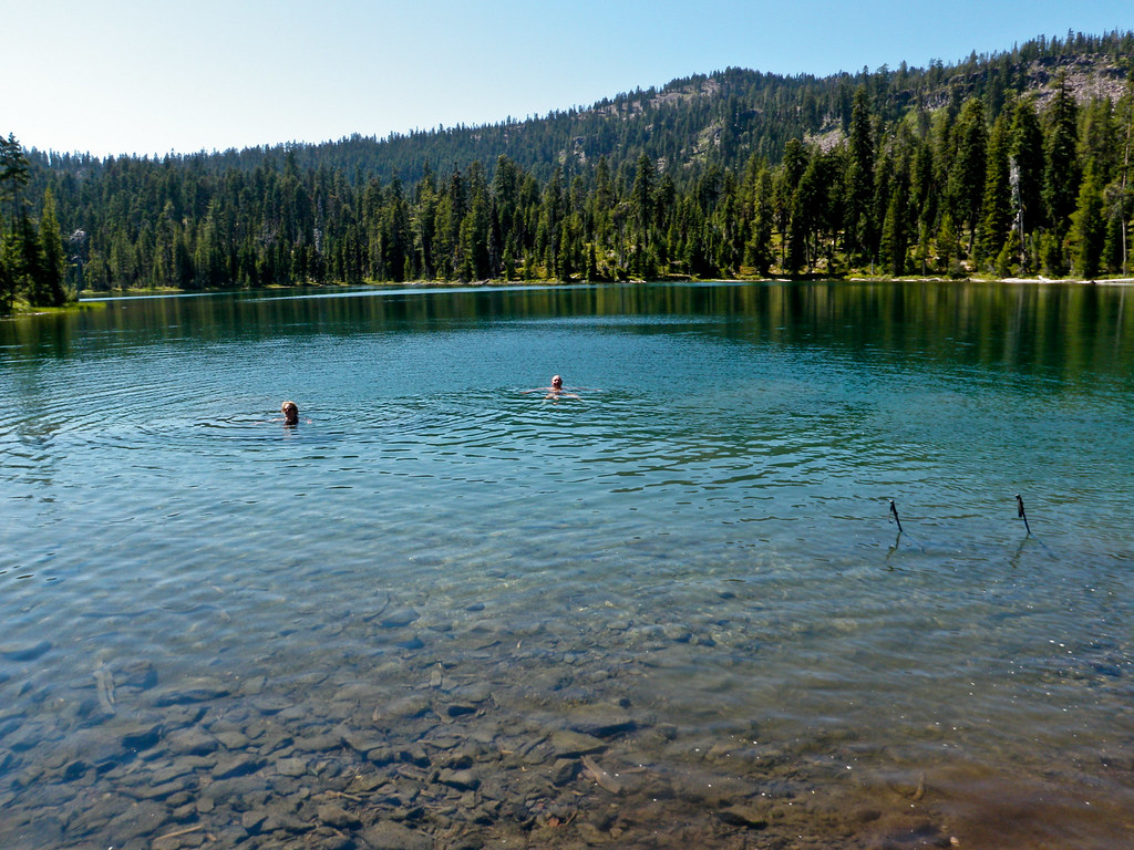 Two people enjoying a dip in Trapper Lake on a sunny day.