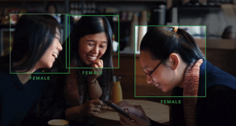 Three Asian women laughing at a cafe with image detection identifying them as female.