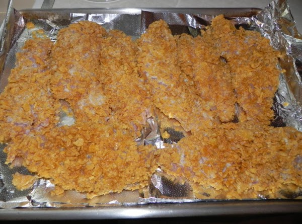 Dip chicken into remaining milk mixture; roll in the remaining cornflakes and place in...