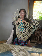 Photo: Healthcare volunteer worker, Noi, making baskets for sale. Chiang Dao