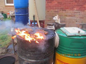 Photo: The oven goes on top of these two drums. Waters boiling , Ellie Dogy bones alight, hot stove