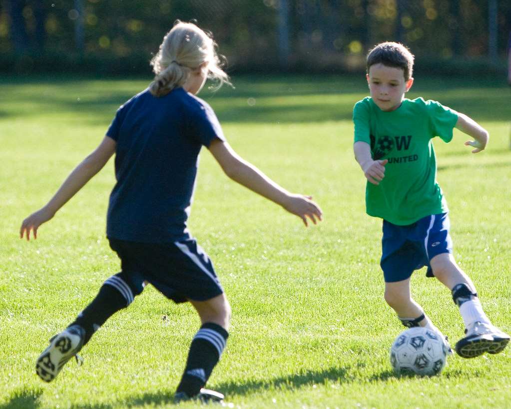 Boy running at a girl with a soccer ball