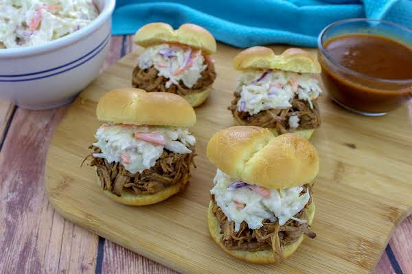 A Tray Of Brisket Sandwiches With Gravy On The Side.
