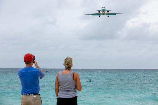Tourists on Maho Beach watch a plane approach the notoriously short runway on St. Maarten.