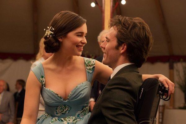 梳著髮髻、穿著低胸藍禮服的女子低頭望著輪椅上的男人,兩人相視而笑。