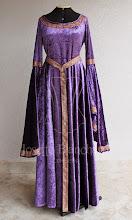 Photo: Vestido Medieval em veludo molhado violeta com detalhes e cinto em galão violeta e dourado. Ajustável nas costas. A partir de R$ 300,00.