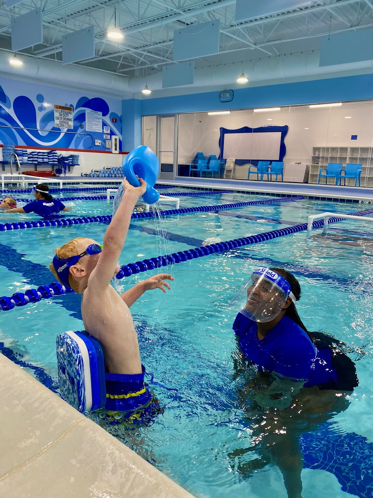 Swim Instructor wearing face shield in pool as Personal Protective Equipment (PPE)