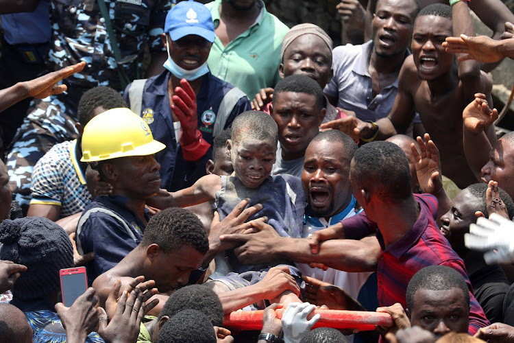 Men carry a boy who was rescued at the site of a collapsed building containing a school in Nigeria's commercial capital of Lagos, Nigeria on March 13 2019. Picture: REUTERS/Temilade Adelaj