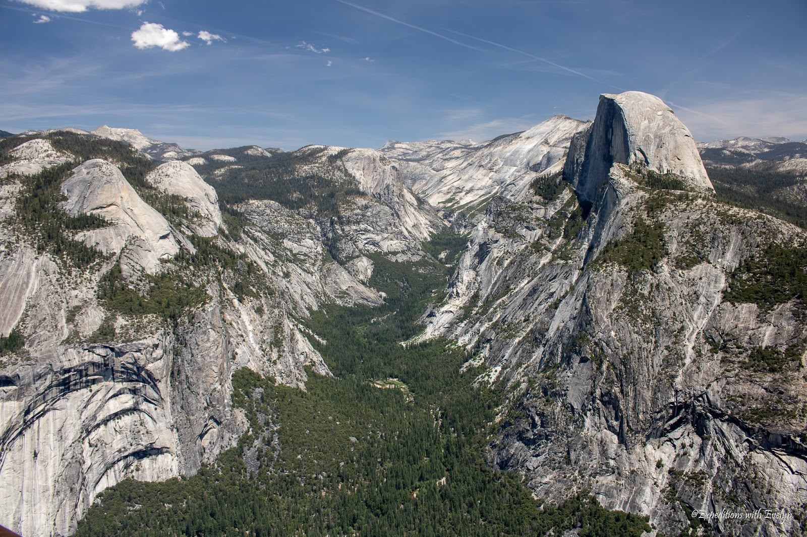 Granite rocks forms a U-shaped valley filled with greenery.  Yosemite's scenery make it a sought after National Parks Reservation 2021.