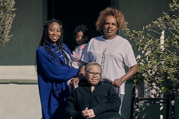 Family portrait of Keiara with her daughter, mother, and grandmother in front of the home they share.