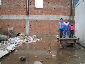 Photo: Note the path of bricks to get through the water and the pigs in the garbage. This is in a city Maqu in very southern Gansu province. I was there for the occasion of a traditional horse race (see other photos).