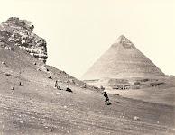 2 mannen op een steenberg naast een piramide